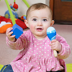 A stock photo of a happy looking babby in a pink sweater playing with a maraca
