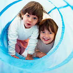 A stock image of two toddler-aged children crawling through and playing in a slide