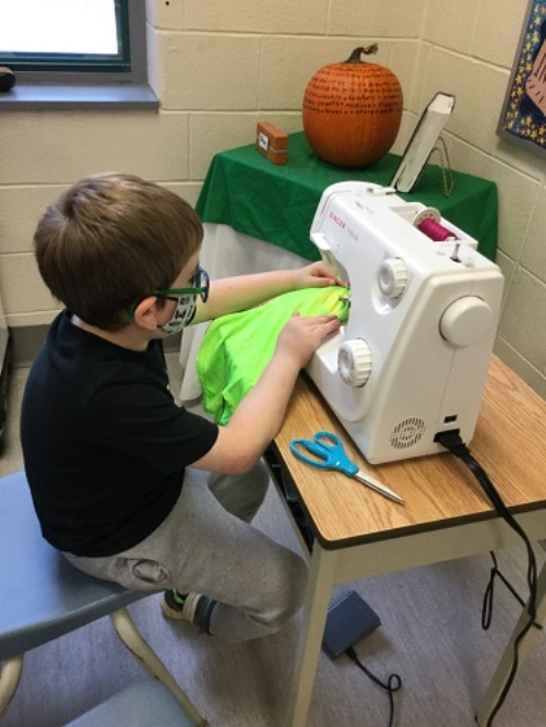 Child using a sewing machine to sew a t-shirt into a halloween bag