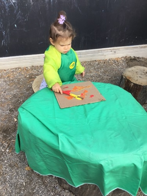 Child sitting at a table outside painting with yellow, orange and red paint